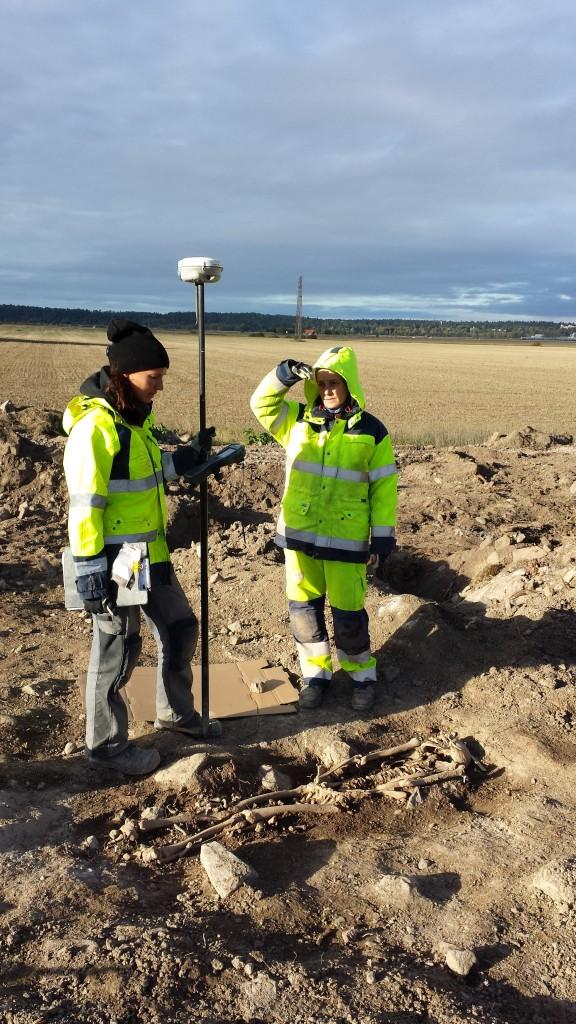 Emma Sjöling och Sofia Prata mäter in skelettet i en av gravarna som undersöktes. Foto: SAU/Upplandsmuseet.