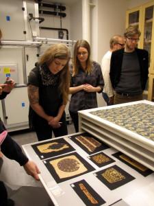 Textilier. I lådan tidigkristna koptiska broderier från Egypten, ovanpå bordet ett medeltida tyg ffrån Funbo, Uppland
