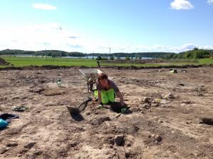 Sanna Eklund undersöker boplatsen. Bakom henne skymtar Edssjön.