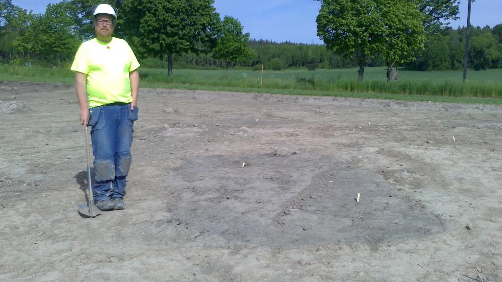 Arkeologen Ulf Celin vid ett av grophusen. Anar du ingången i hörnan längst fram till vänster?