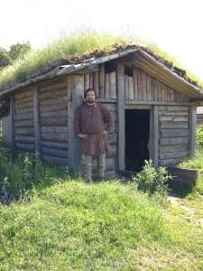 Så här kan grophus ha sett ut under vikingatiden. Rekonstruktionen finns på Gunnes gård, där arkeologen Anders Liliehöök, som står vid dörröppningen, är verksam.