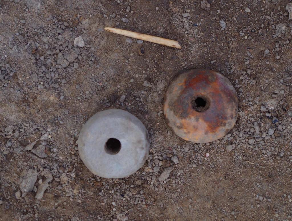 Två av de sländtrissor som Sanna hittat, en av sten och en av ben/horn. Intill ligger en bennål.
