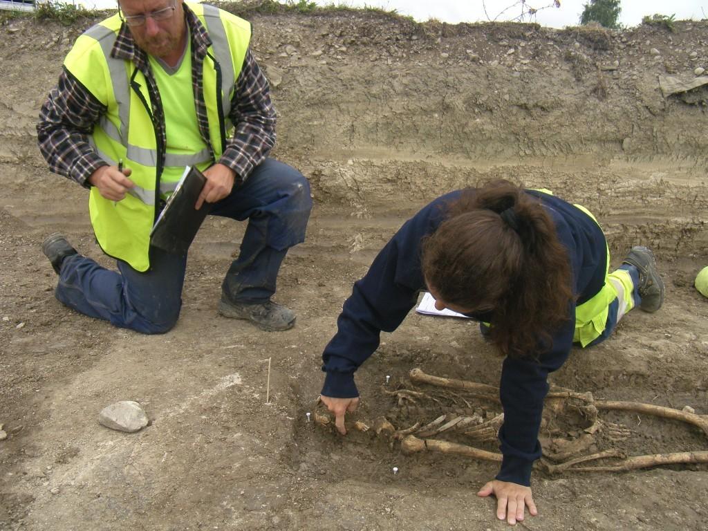 Arkeolog Ulf Celin och osteolog Sofia Prata undersöker och diskuterar skelett.